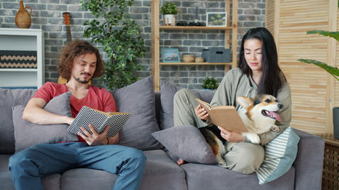 Young husband and wife reading books at home and stroking corgi puppy Archivo