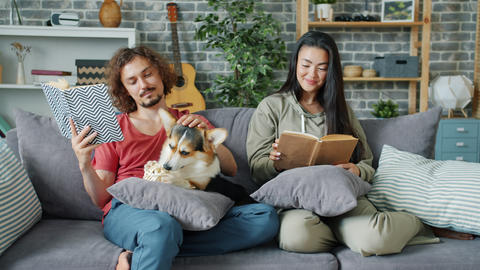 Husband and wife enjoying books at home and caressing adorable corgi puppy Archivo