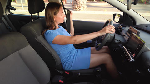 Woman in blue dress fastening car safety seat belt while sitting inside of Footage