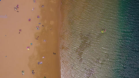 View from the height of the golden sand, sun umbrellas, unrecognizable people on Footage