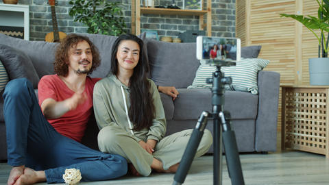 Young couple recording video for internet vlog in apartment using smartphone Footage