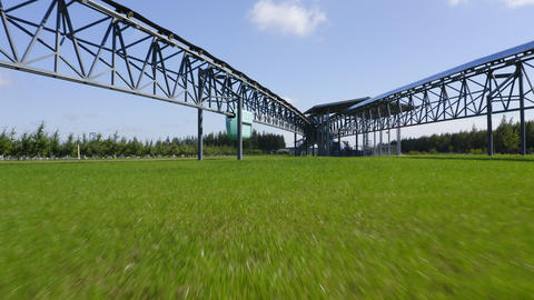 close upper motion over grass to skyway transport under sky Live Action
