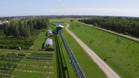 skyway vehicle drives past garden and greenhouses aerial Live Action