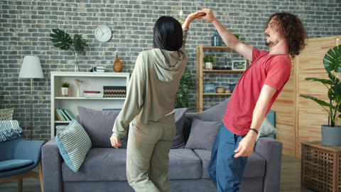 Adorable mixed-race couple dancing at home laughing enjoying happy moments Footage