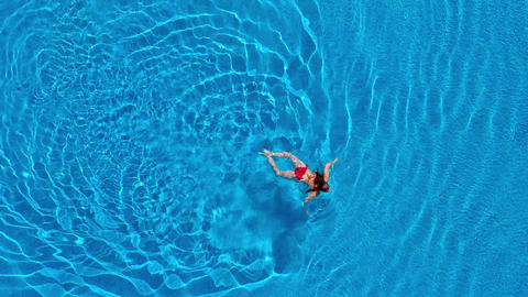 View from the top as a woman in red swimsuit swims in the pool Footage