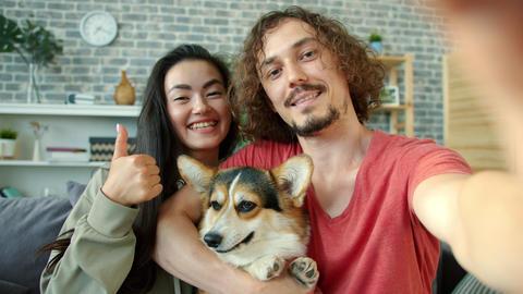 Joyful girl and guy taking selfie with corgi dog having fun making funny faces Archivo