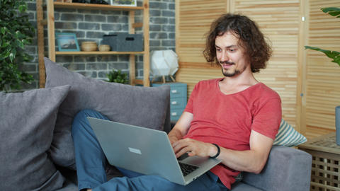 Smiling guy using laptop on couch at home typing smiling working online Live Action