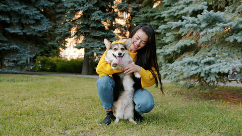 Slow motion of cute Asian girl hugging corgi dog in park on autumn day Footage