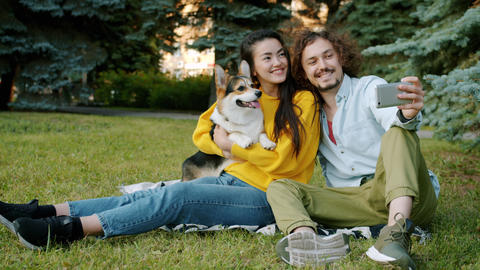 Girl and guy taking selfie with corgi puppy using smartphone in city park Archivo