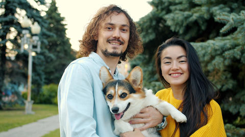 Portrait of man and woman holding corgi puppy outdoors in city park smiling Archivo