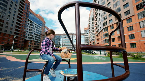Little girl play on park playground with a carousel. A lonely child is riding a GIF