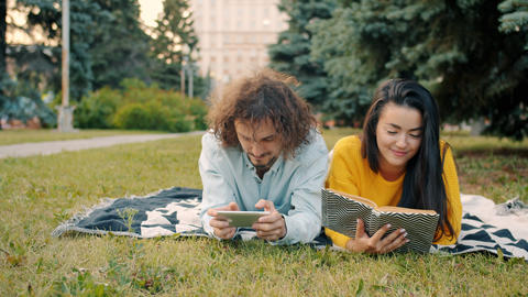 Couple relaxing outdoors in park with dog playing smartphone game and reading Archivo