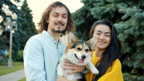Beautiful young couple kissing small corrgi dog then smiling in city park Archivo