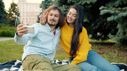 Portrait of funny young couple girl and guy taking selfie outdoors in city park Archivo