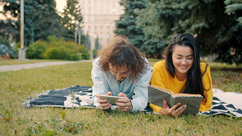 Man playing smartphone game while woman reading book outside in urban park Live Action