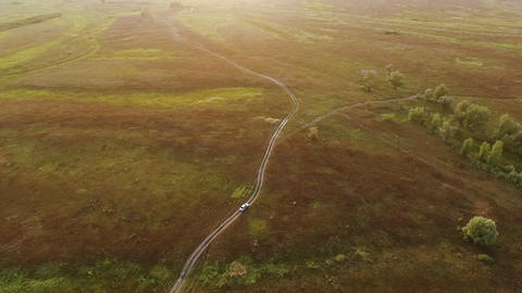 White car on scenic unpaved road aerial tracking on sunset with horizon reveal Live Action