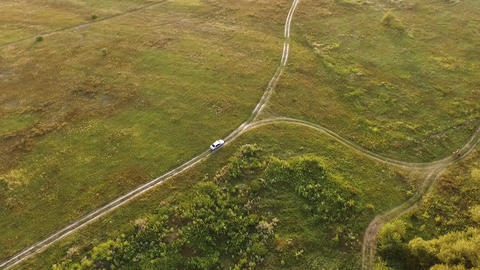 White car on scenic unpaved road with fork aerial tracking shot on sunset Live Action