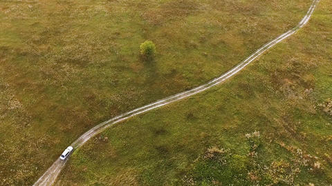 White car on scenic unpaved road aerial tracking shot on sunset Live Action