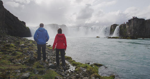 Couple hiking in nature hike by Iceland waterfall Live Action