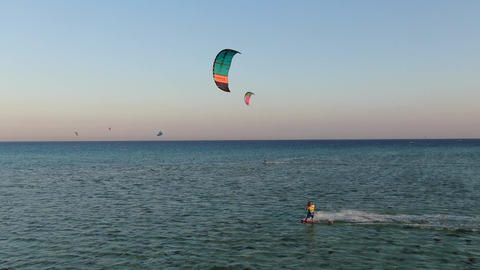Kite surfers are gliding on high speed in the sea during sunset, aerial footage Live Action