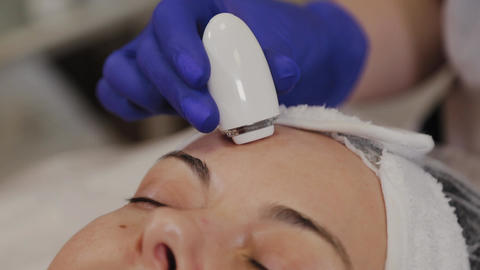 A professional beautician measures the condition of the skin using an instrument Footage
