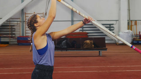 Pole vaulting indoors - young woman with pigtails preparing for the jump - Live Action