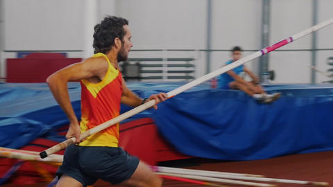 Pole vaulting indoors - a man in yellow shirt running up and jump over the bar Live Action