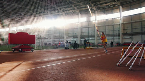 Pole vaulting indoors - a man in yellow shirt performing a jumping over the bar Live Action