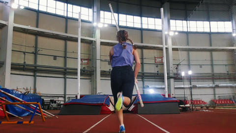 Pole vaulting in the indoors stadium - young woman with pigtails jumping over Live Action