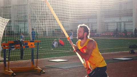 Pole vaulting indoors - a man in yellow shirt running up before the jumping Live Action