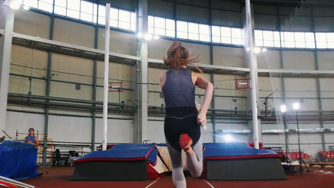 Pole vaulting indoors - a young woman with ponytail running up and jumping over Live Action