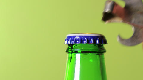 A hand opening a green bottle of beer over green backgound Live Action