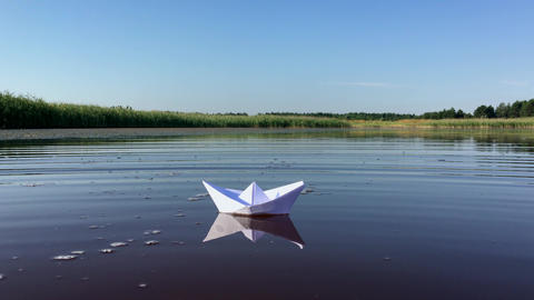 Small white paper ship floats away into the distance on the lake Footage