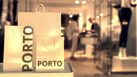 Paper shopping bags with Porto caption against blurred store entrance. Retail in Live Action
