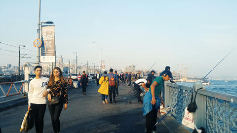 People walking on Galata bridge which is one of the famous travel destinations. Daily life in Live Action