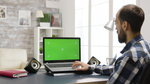 Over the shoulder zoom in shot of man looking at laptop with green screen Live Action