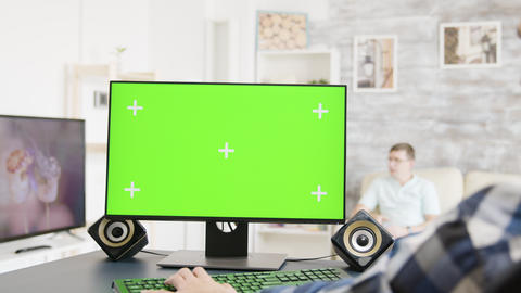 Man working on green screen PC display in bright and modern flat Footage