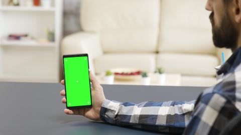 Man holding a phone with green screen in modern and bright living space Footage