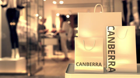 Paper shopping bags with Canberra caption against blurred store entrance. Retail Live Action