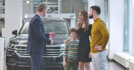 Caucasian car dealer standing in front of new car and congradulating young Live Action