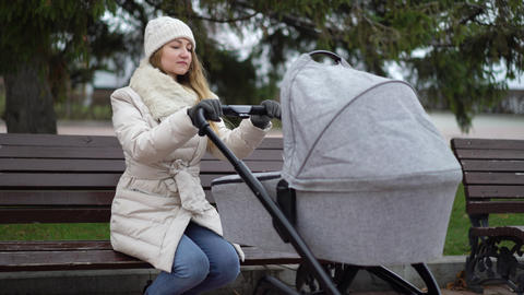 Young mother with newborn child outdoor. She sitting on the bench with baby Live Action