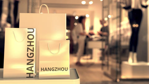 Paper shopping bags with Hangzhou caption against blurred store entrance. Retail Live Action