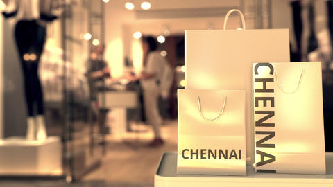 Paper shopping bags with Chennai caption against blurred store entrance. Retail Live Action