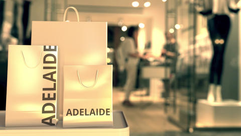 Paper shopping bags with Adelaide caption against blurred store entrance. Retail Live Action