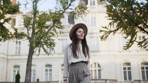 Beautiful young woman in stylish hat walking near the luxurious mansion on sunny Live Action