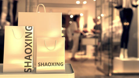 Paper shopping bags with Shaoxing caption against blurred store entrance. Retail Live Action