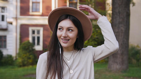 Gorgeous smiling modern woman in stylish hat walking nearby beautiful rich Live Action