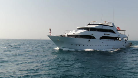 Aerial shot of a big cruise ship in Dead Sea, young woman on the ships bow Live Action