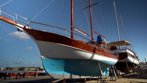 Retro ship under restoration. A wooden colorful ship stands on land. Repair of Live Action