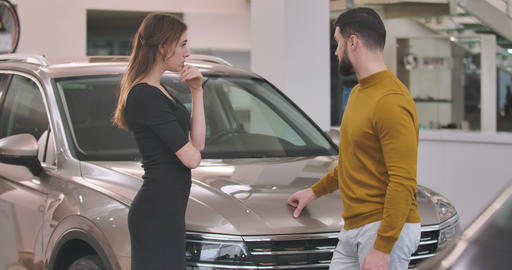 Young Caucasian couple standing in car dealership and choosing new automobile Live Action